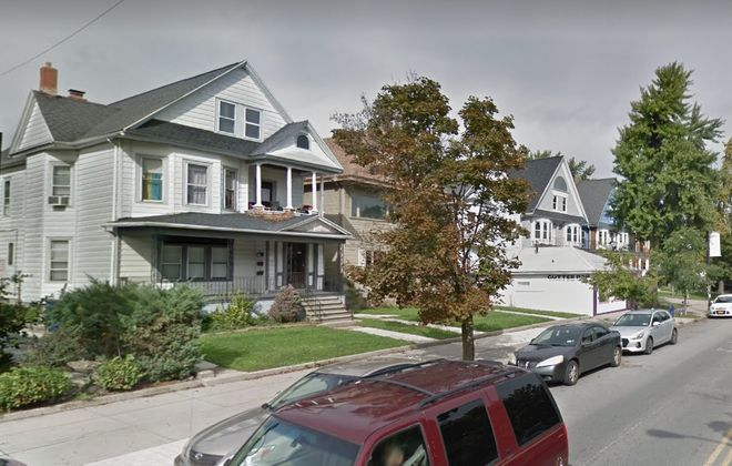 The three adjacent houses on Elmwood that would be demolished to make way for a four-story development of market-rate apartments and retail space. (Google image)