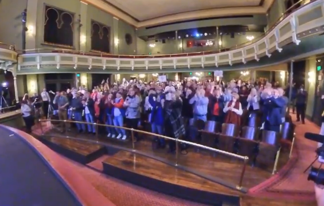 "Residents of Fredonia celebrate as they react to the live-streamed announcement that the village is one of five finalists for the next season of reality TV show ""Small Business Revolution."" (Screenshot of SUNY Fredonia Facebook video)"