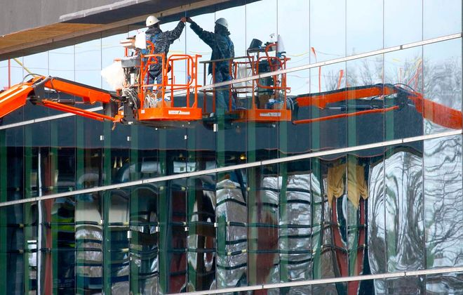 A worker places framing trim pieces into the joints around reflective windows on a building in the new expansion project at Moog. (Robert Kirkham/Buffalo News)