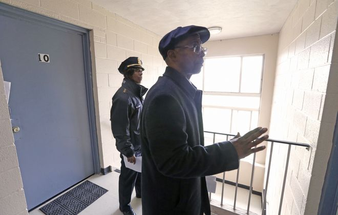 Police Commissioner Byron C. Lockwood, right, and Deputy Commissioner Barbara Lark talk to a resident in the Towne Gardens Apartments after a shot fired during a dispute in a nearby parking lot killed a 12-year-old boy last year. Though not charged in that killing, an alleged member of a gang operating around the complex faces trial next week in two other murders. (Robert Kirkham/News file photo)