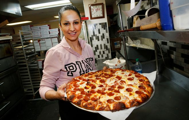 Thick cheese covers the crust of the cheese and pepperoni pizza being held by Ricotta's Pizza co-owner Marie Khoury. (Robert Kirkham/Buffalo News)