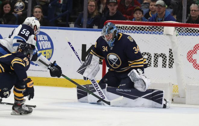 Buffalo Sabres goaltender Jonas Johansson (34) makes a save against Winnipeg Jets center Jansen Harkins (58) in the first period at Key Bank Center in Buffalo,N.Y. on Sunday, Feb. 23, 2020. (James P. McCoy/Buffalo News)