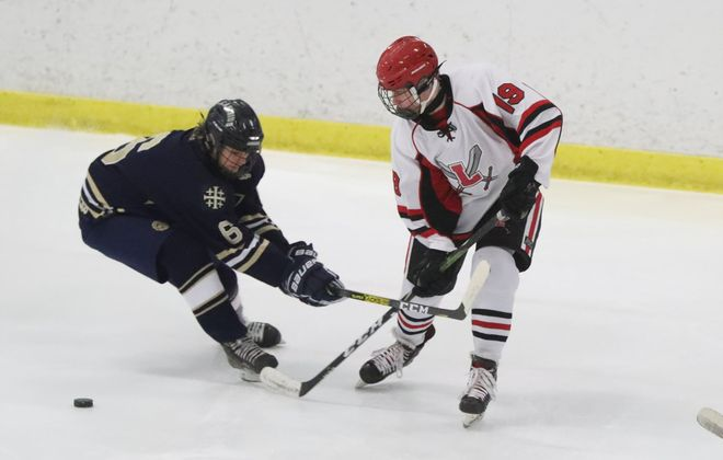 Canisius Luke Braun battles Lancaster's Preston Schlager for the puck in the first period at Northtown Center Saturday. Canisius won, 3-1. (James P. McCoy/Buffalo News)