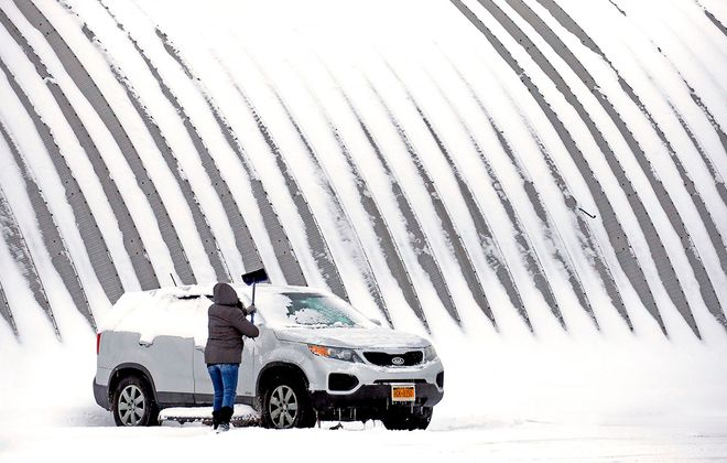 After finishing her shift at Smokin' Joes Trading Post in Sanborn, Theresa John cleans the fresh snow off her family's car next to one of the company's Quonset Hut styled buildings on Friday, Feb. 7, 2020. (Robert Kirkham/Buffalo News)