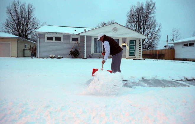 Dawn Robinson shovels snow at her home on  Glenhurst Road in the Town of Tonawanda on Thursday, Feb. 6, 2020. (John Hickey/Buffalo News)