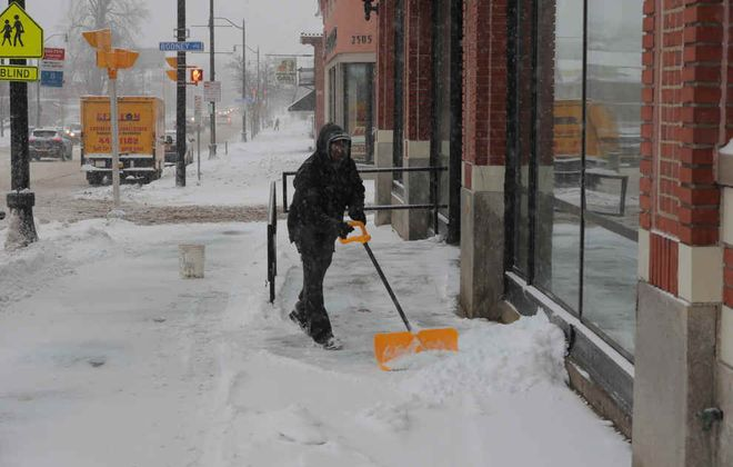 Michael Drayton, a maintenance worker at Tri-Main Center, shovels snow Friday. (John Hickey/Buffalo News)