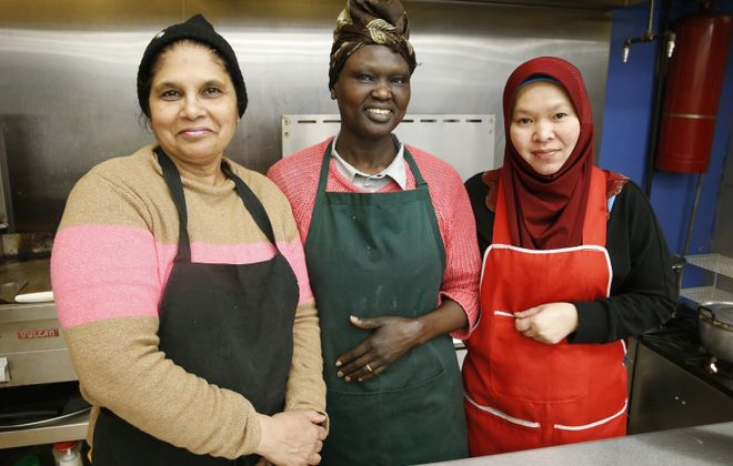 From left, Sholmeat Robin, from Pakistan; Aniwang Berrie, from Sudan; and Pranon Wanwian, from Thailand, share a kitchen at the Grant Street Bazaar, an international food hall at 68 Grant St. (Robert Kirkham/Buffalo News