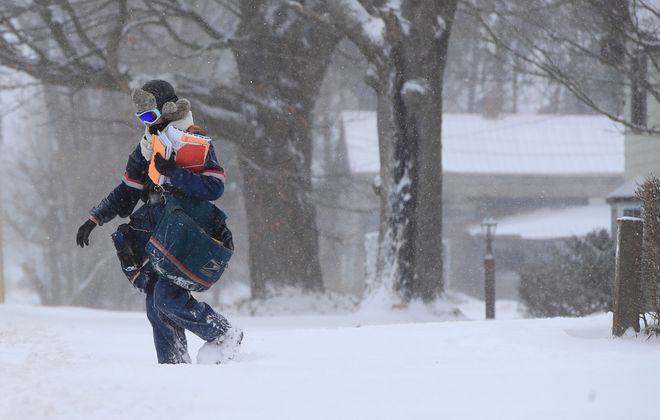Renee' Potzler, Postal carrier delivers mail along Newman Street in Springville last month. Chances are slim we'll get another storm like this one, so Amherst is lifting its winter parking ban. (Harry Scull Jr./Buffalo News)