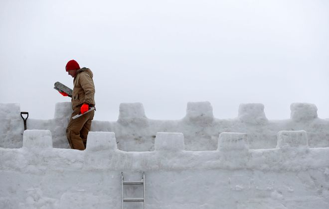 Jim Warner works on the top part of the ice castle being built for this weekend's annual winter festival in Mayville. This is the first year they are building it out of snow because the ice on Chautauqua Lake wasn't thick enough. (Mark Mulville/Buffalo News)