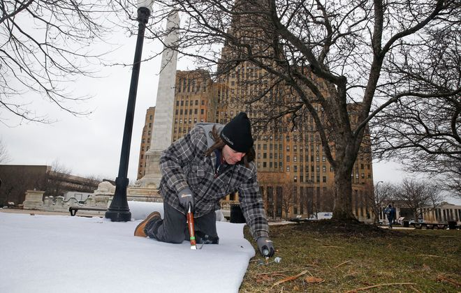 """Special effects technician Jim Kerr tacks down rolls of fake snow in Niagara Square for the filming of """"Nightmare Alley."""" (Robert Kirkham/Buffalo News)"""