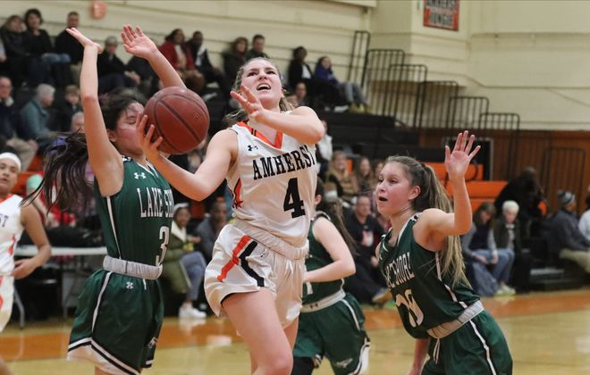 Amherst's Ella Wanzer scores two points over Lake Shore's Jadyn Jones in the second half at Amherst high school in on Friday, Feb. 28. (James P. McCoy/Buffalo News)