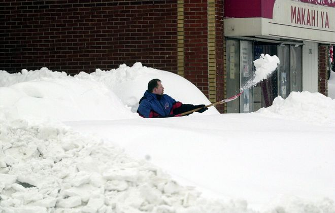 "Armed only with a shovel, Joe Manning of South Buffalo, searches for his snow buried car on Dec. 28, 2001. The record 82"" of snow which fell during Christmas week 2001 was accompanied by far less blowing snow (and, therefore, was not a blizzard). (Robert Kirkham/Buffalo News file photo)"