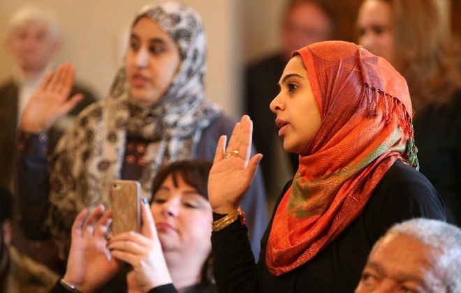 Indian immigrant Femida Manjara, right, takes the oath of allegiance during a naturalization ceremony in Buffalo in 2013. The Trump administration's harsh new limits on immigration will hurt Buffalo. (Robert Kirkham/News file photo)