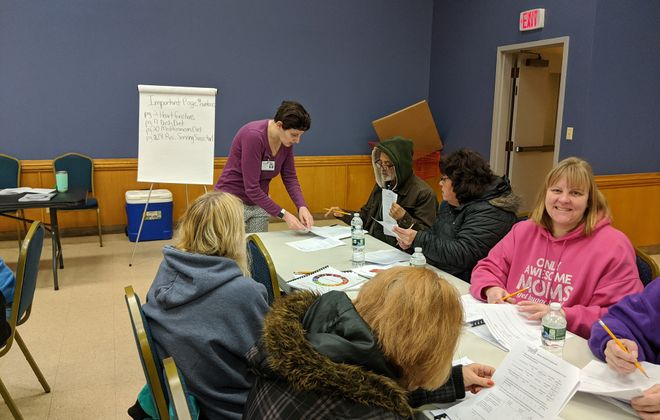 Laura Steuerman, rear, Catholic Charities nutrition educator, helps Nutrition Simply Said participants complete food surveys during a recent nutrition training at the Russell J. Salvatore Food Pantry and Outreach in Lackawanna. (Photo courtesy of Catholic Charities)