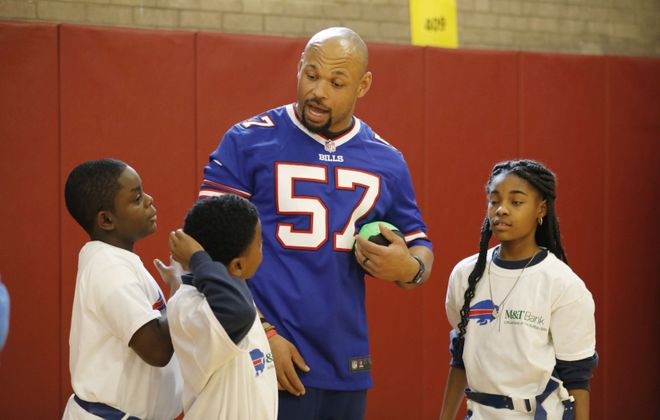 Buffalo Bills player Lorenzo Alexander. who retired after the 2019 season, goes over a play during a flag football game with students following an announcement of a 5-year continuation of the partnership between M&T Bank and the Buffalo Bills at Highgate Heights Elementary School PS 80 last March. (Derek Gee/Buffalo News)