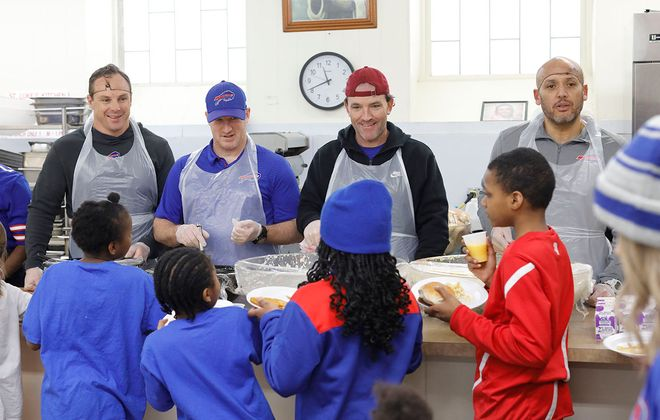 Members of the Buffalo Bills coaching staff, from left, special teams coordinator Heath Farwell, assistant special teams coach Matthew Smiley, defensive backs coach John Butler and defensive assistant coach Jimmy Salgado serve lunch to students from Our Lady of Hope while volunteering with colleagues from the Bills coaching staff at St. Luke's Mission of Mercy Friday (Derek Gee/Buffalo News)