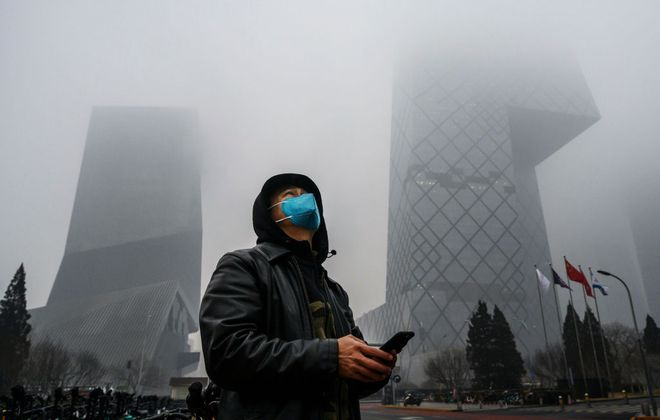 A Chinese man wears a protective mask as he stands near the CCTV building in fog and pollution during rush hour in Beijing's central business district on Feb. 13, 2020. (Getty Images)