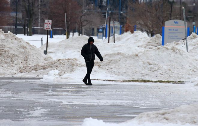 A pedestrian walks carefully through an icy parking lot at UB's North Campus. (John Hickey/News file photo)