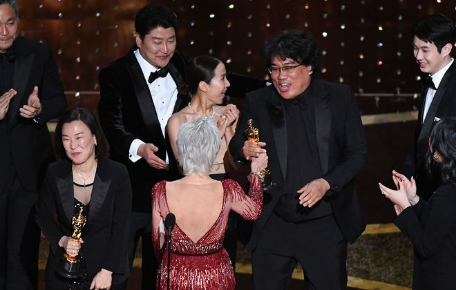 """Parasite"" producers Kwak Sin-ae, left, and Bong Joon-ho accept the award for best picture Sunday during the 92nd Oscars at the Dolby Theatre in Hollywood. (Mark Ralston/AFP via Getty Images)"