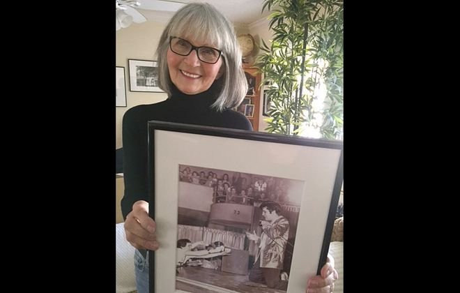 Montez Thalman and the iconic Robert L. Smith photo that she keeps her on wall. That's Elvis Presley, in Buffalo, kneeling for a teenage Thalman. (Image courtesy Montez Thalman)
