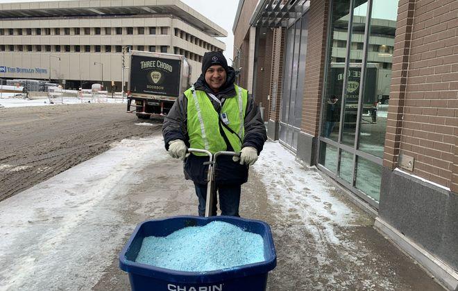 Tyler Berns pushes a salt spreader on a sidewalk in front of the Buffalo Harborcenter Marriott Thursday, Feb. 27, 2020. (Maki Becker/Buffalo News)