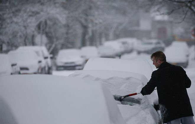 Nick Galasso scrapes the layers of ice and snow off his windshield Thursday on Norwood Avenue. (Derek Gee/Buffalo News)