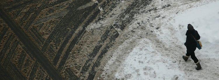 A pedestrian navigates through snow and slush while crossing Pearl Street at Chippewa. (Derek Gee/News file photo)