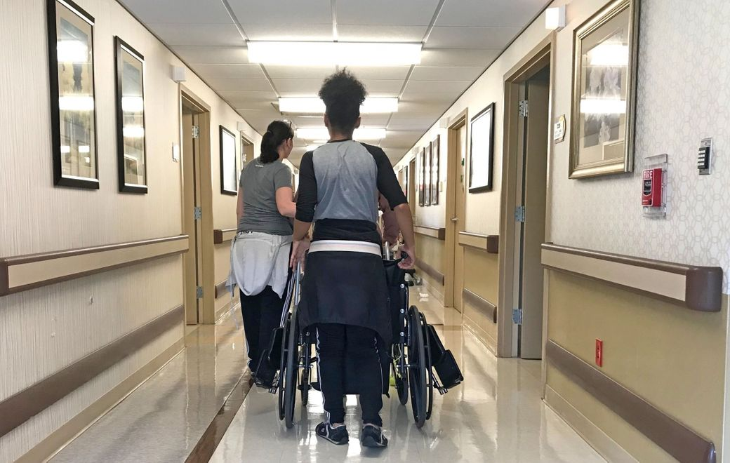 Caregivers transport a resident down a hallway at Absolut Care of Aurora Park in East Aurora in May 2018. (Robert Kirkham/News file photo)