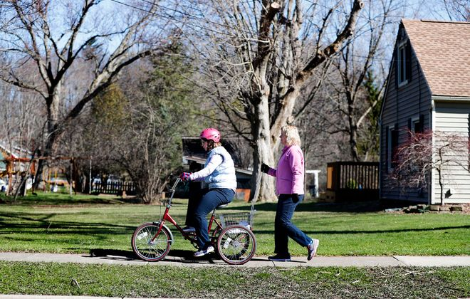Elizabeth Moore rides her tricycle under the watchful eye of her mother, Sharon, near their home in East Aurora. (Mark Mulville/Buffalo News)