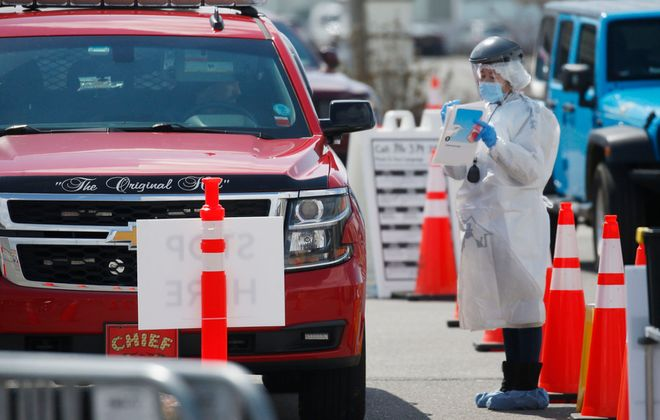 A professional medical tester communicates with a driver as drive-up patients were tested for Covid-19 in a section of the Walmart parking lot on Walden Avenue in Cheektowaga on Wednesday, April 15, 2020. (Robert Kirkham/Buffalo News)