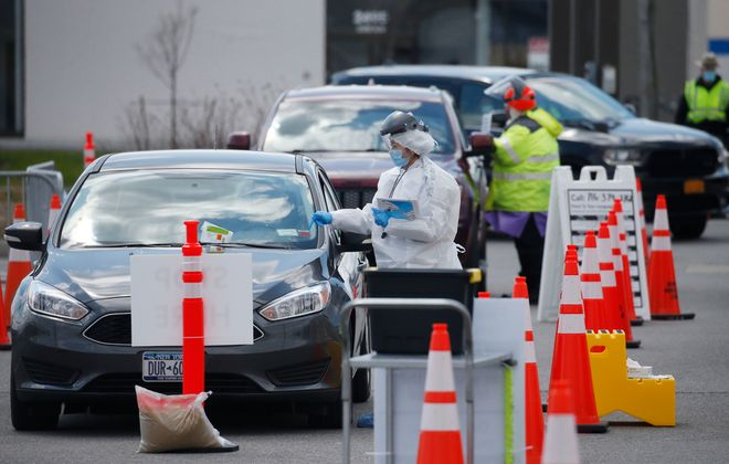 A professional medical tester communicates with a driver as patients are tested for Covid-19 in Cheektowaga. (Robert Kirkham/Buffalo News)