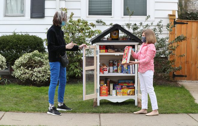 Lizzie Lester, 10, has established a small community pantry outside her house on Parker Avenue in Buffalo. Elizabeth Verel, whose brother died last week of Covid-19, was interested. (James P. McCoy/Buffalo News)