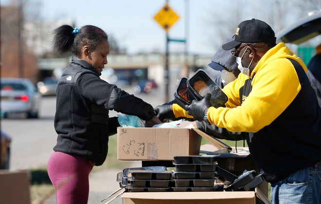 Kim Young, of Buffalo, who was laid off from her job during the Covid-19 outbreak and whose husband's hours were cut, gets free meals for her family Wednesday, April 1, 2020. The meals are being distributed by Buffalo Peacemakers and Stop the Violence every Wednesday at Genesee and Kilhoffer streets. Here, Michael King, left, and Anthony James of the Peacemakers help out. (Sharon Cantillon/Buffalo News)
