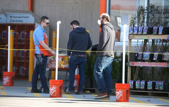 A customer wearing a N95 mask walks through a social distancing gauntlet near the Home Depot main entrance at the Hamburg store near McKinley Mall as store employees set up a temporary corral that goes into effect this Friday. (Robert Kirkham/Buffalo News)