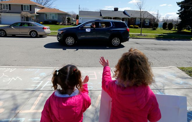 June and Maizey Lazarz wave to their teachers during a parade of Maple West Elementary teachers and staff on the streets of Amherst on April 2, 2020. (Mark Mulville/Buffalo News)