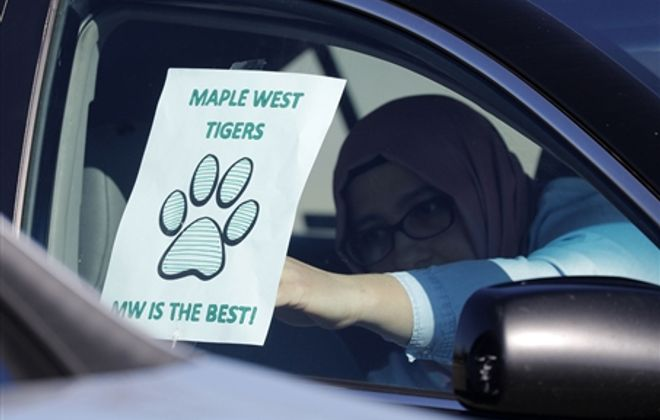 Parade of Maple West teachers drives by students' homes