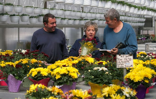 Owners Les and Lynda Draudt and their son Brad, at left, select an assortment of Easter flowers that will be delivered to hospitals and nursing homes. The Draudts, who own Draudt's Farm Market in Hamburg, received a $10,000 donation after many flower orders were canceled. (Robert Kirkham/Buffalo News)