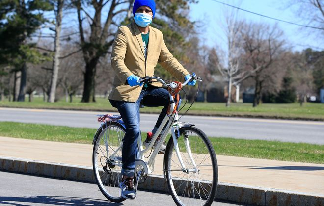 Hari Upreti rides his bike along Bailey Avenue on Monday, April 6, 2020. (Harry Scull Jr./Buffalo News)