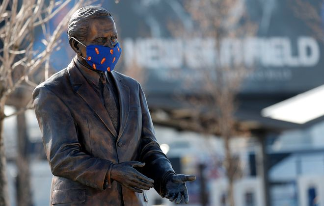 The statue of Ralph Wilson  wears a face mask at New Era Field in Orchard Park. (Mark Mulville/Buffalo News)