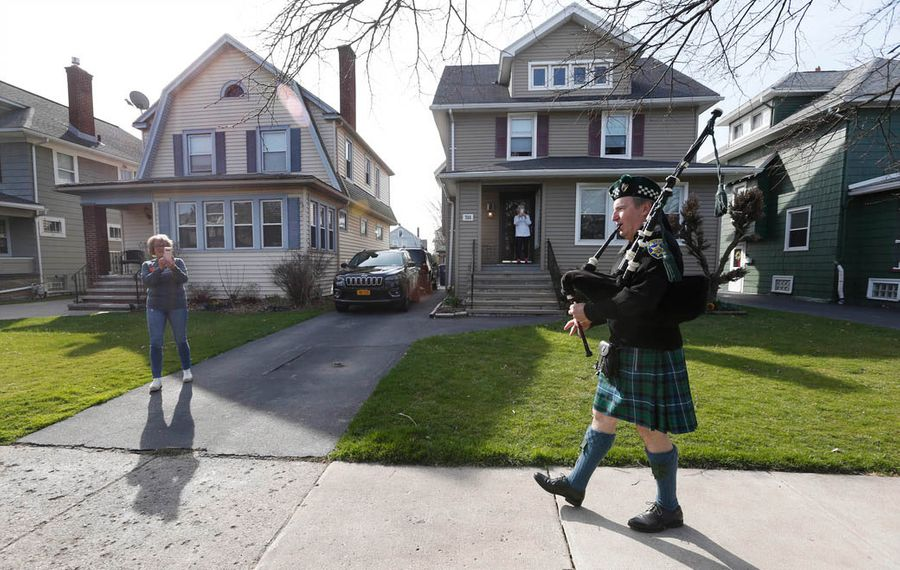 Dan Ryan plays outside every evening in his Scottish garb to cheer up Buffalo area residents during the Covid-19 pandemic. He walks up Parkside Avenue while playing in the North Buffalo neighborhood, Monday, April 6, 2020. Ryan, a member of the Erie County Sheriff Pipes & Drums, picks different neighborhoods to walk through as he plays. (Sharon Cantillon/Buffalo News)