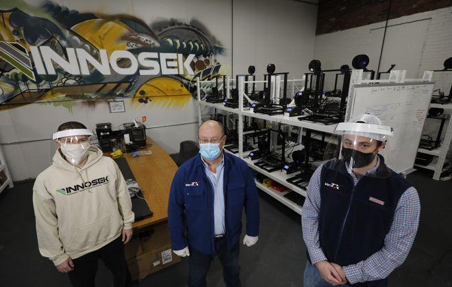 Brian Bischoff, VP of Innosek, left, joins James and Keaton Regenor of Innosek customer Rapid Medical Parts at the 3D printer's Tonawanda facility. (Derek Gee/News file photo)