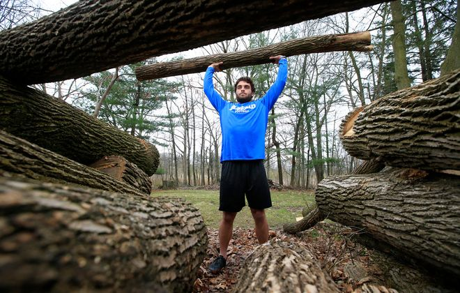 University at Buffalo football player Alex McNutly stays in shape with his log-lifting workout in his backyard during the Covid-19 pandemic on Wednesday, April 8, 2020. (Harry Scull Jr./Buffalo News)