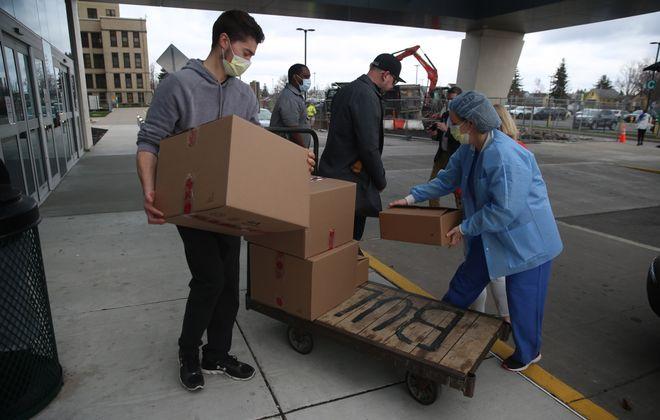 Brett McCarthy and Karen Schurr unload supplies donated by New Era Cap at Erie County Medical Center on April 10. (John Hickey/Buffalo News)