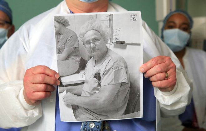 Buffalo General Medical Center X-ray technologist Lynn Siener holds a picture of her late colleague John Poleon who passed away from COVID-19 after contracting it while working in the hospital. (Harry Scull Jr./Buffalo News)