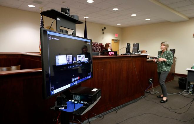 Court clerks take care of paperwork as Erie County Court Judge Sheila DiTullio presides over a virtual hearing on a screen using Skype in Buffalo on April 30, 2020.   (Mark Mulville/Buffalo News)