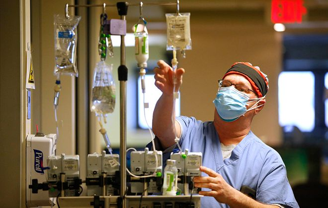 Registered Shawn Covell hangs sedatives and pain medication for a patient in the Covid-19 ICU at Buffalo General Medical Center, Tuesday, April 21, 2020. (Sharon Cantillon/Buffalo News)