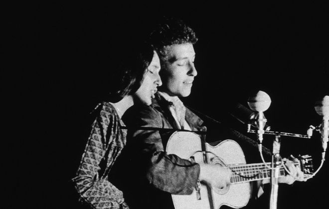 American folk singers Joan Baez and Bob Dylan perform together onstage in 1963. (Columbia Records/Getty Images)