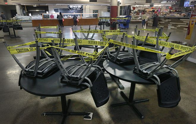 Chairs are put on tables and a more open floor plan is in use at the Broadway Market to promote social distancing. (John Hickey/Buffalo News)