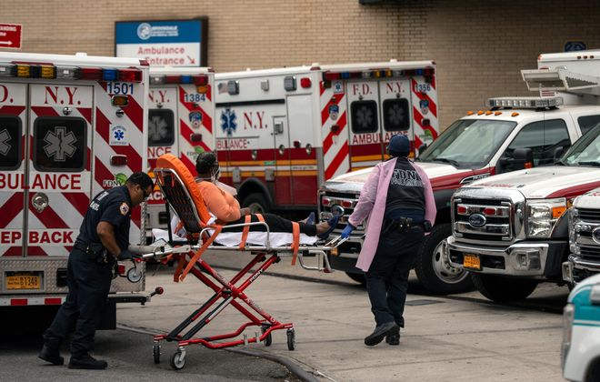 Paramedics transport a patient brought by ambulance to Brookdale Hospital Medical Center in Brooklyn last week. New York City's death toll from Covid-19 is staggering, but gradually declining. (New York Times)