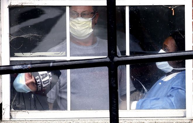 Staffers inside Safire Rehabilitation of Northtowns nursing home in the Town of Tonawanda watch from a window Friday as fellow union members protest over a lack of personal protective equipment. (Robert Kirkham/Buffalo News)